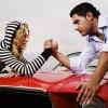 Couple Arm Wrestling on Car Hood --- Image by © Serge Kozak/zefa/Corbis
