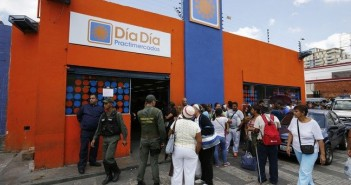 People line up to buy basic products at Dia Dia supermarket in Caracas