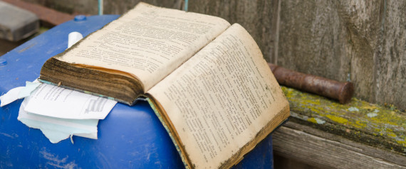 Solodniki, Russia - May 13, 2015: The old open book lying on a barrel at the rustic fence